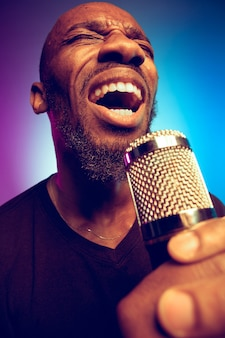 Jovem músico de jazz afro-americano cantando uma música em gradiente roxo-azulado