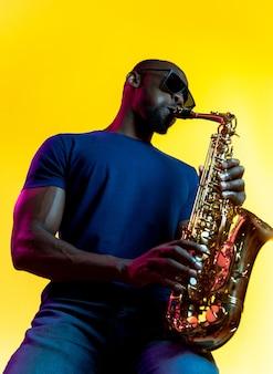 Jovem músico de jazz afro-americano tocando saxofone em fundo amarelo studio em luz de néon da moda. conceito de música, hobby. cara alegre improvisando. retrato colorido do artista.