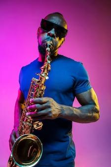 Jovem músico de jazz afro-americano tocando saxofone no fundo rosa do estúdio em luz de néon da moda. conceito de música, hobby. cara alegre improvisando. retrato colorido do artista.