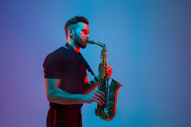 Jovem músico de jazz caucasiano tocando saxofone em estúdio gradiente azul púrpura