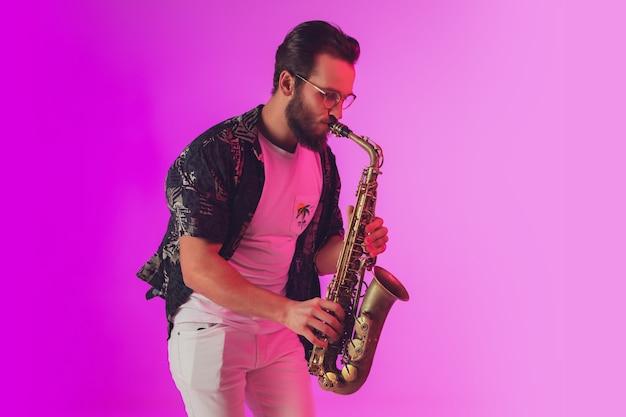 Jovem músico de jazz caucasiano tocando saxofone em fundo de estúdio rosa gradiente em luz de néon. conceito de música, hobby, festival. cara alegre, alegre e atraente. retrato colorido do artista.