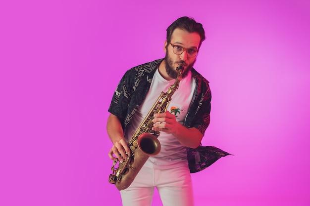 Jovem músico de jazz caucasiano tocando saxofone em luz de néon