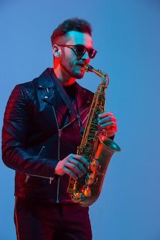 Jovem músico de jazz caucasiano tocando saxofone no fundo do estúdio gradiente azul-roxo em luz de néon. conceito de música, hobby, festival. cara alegre e atraente. retrato colorido do artista.