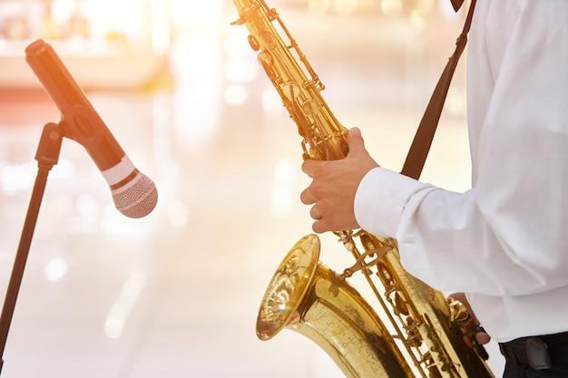 Jovem músico de jazz toca saxofone em um grande salão