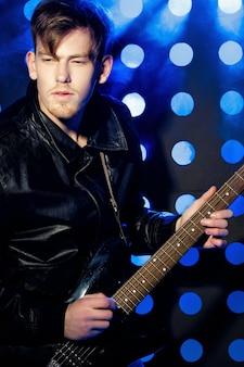 Jovem músico de rock atraente tocando guitarra elétrica e cantando estrela do rock no fundo do spotli ...