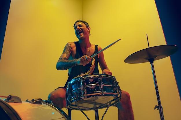 Jovem músico emocional com bateria tocando em fundo amarelo com luz de néon