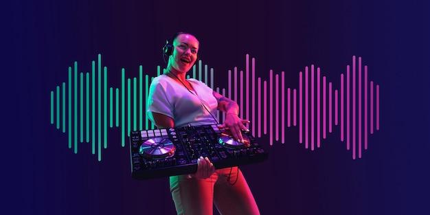 Jovem músico feminino em fones de ouvido no fundo da marinha em luz de néon verde-rosa. conceito de música, passatempo, festival, entretenimento, emoções. arte moderna neon, capa, folheto projetado.