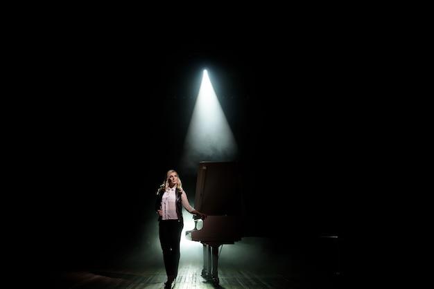 Jovem músico perto do piano de cauda no palco no feixe de luz.