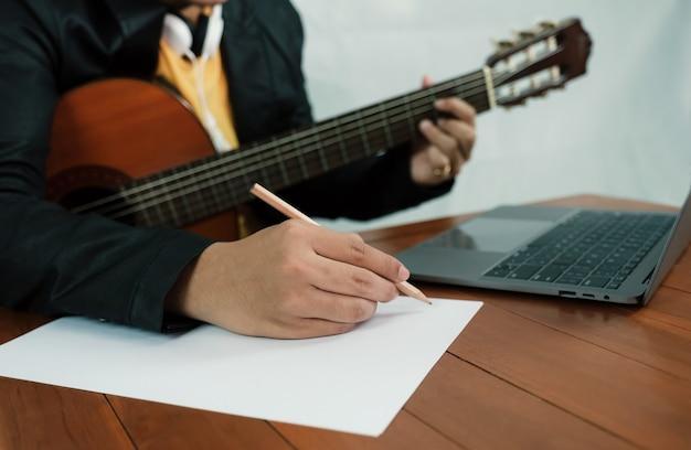 Jovem músico segurando um lápis para fazer anotações em uma aula de música, aprender violão online com um laptop