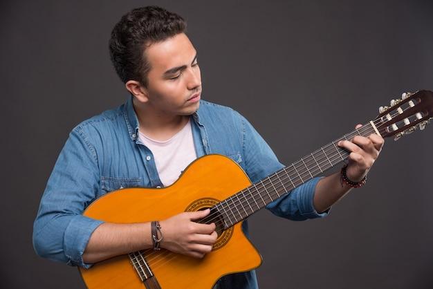 Jovem músico tocando guitarra em fundo preto. foto de alta qualidade