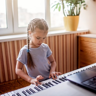 Jovem músico tocando piano digital clássico em casa durante a aula on-line em casa, auto-isolamento