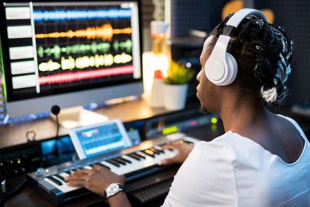 Jovem músico usando fones de ouvido, olhando para as formas de onda do som na tela do computador enquanto pressiona as teclas do teclado de piano