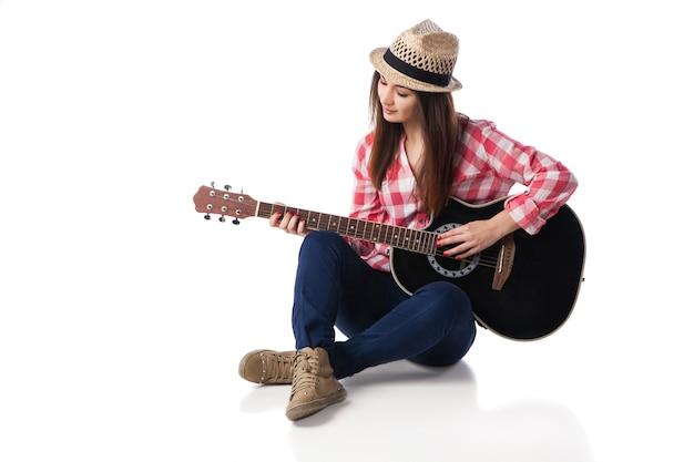 Jovem músico vestindo camisa e chapéu está tocando violão, sentado no chão. fundo branco.