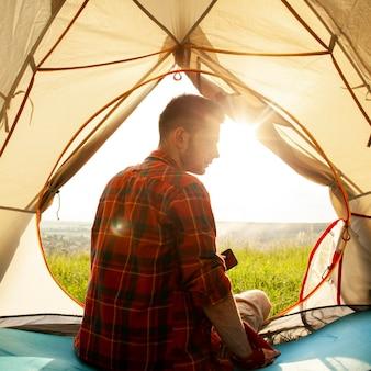 Jovem na barraca de acampamento
