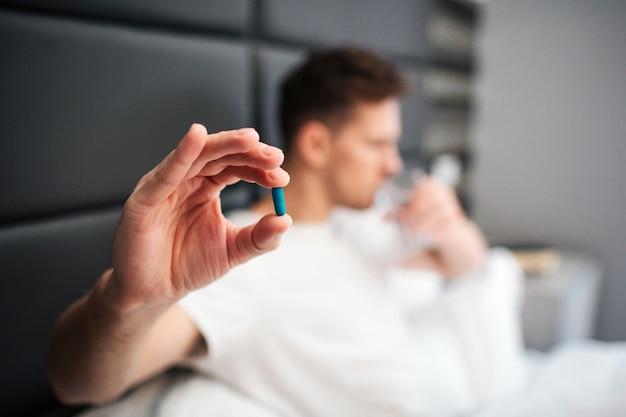 Jovem na cama de manhã cedo. ele segura uma cápsula azul entre os dedos. beba água do copo. luz do dia.