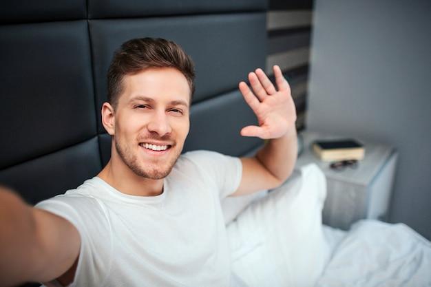 Jovem na cama. ele segura a câmera e sorri. cara acenar com a mão.