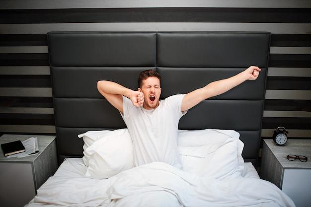 Jovem na cama. ele senta e se estica. cara boceja. de manhã cedo. almofada e cobertor branco.