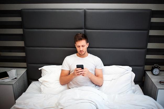 Jovem na cama esta manhã. ele segura o telefone. cara olha para isso. homem sério e concentrado. hora de dormir.
