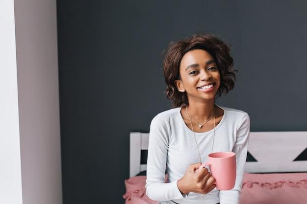 Jovem na cama segurando uma xícara rosa, apreciando o café da manhã, bebendo chá, sorrindo na sala com parede cinza. ela tem cabelo curto e cacheado. vestindo camiseta de mangas compridas cinza claro.
