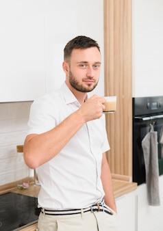 Jovem na cozinha com um cappuccino