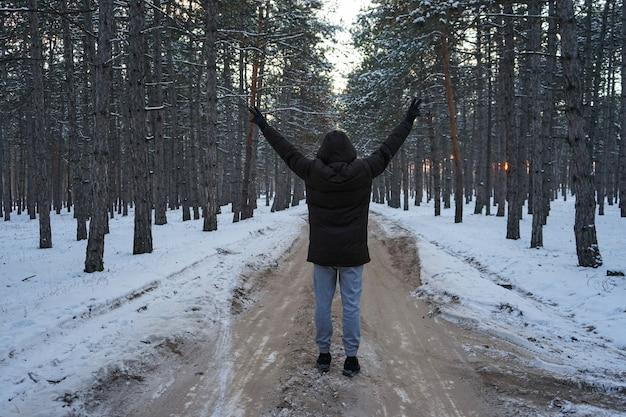Jovem na estrada na floresta de inverno