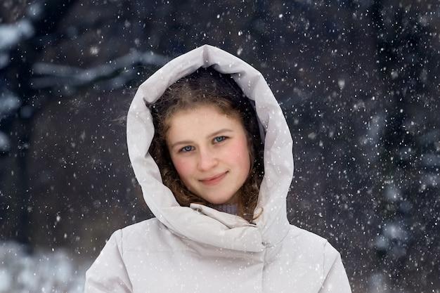 Jovem na floresta de inverno durante uma nevasca. retrato de uma jovem feliz na floresta de inverno
