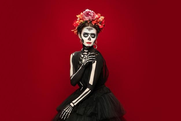 Jovem na imagem da morte de santa muerte santo ou caveira de açúcar com retrato de maquiagem brilhante