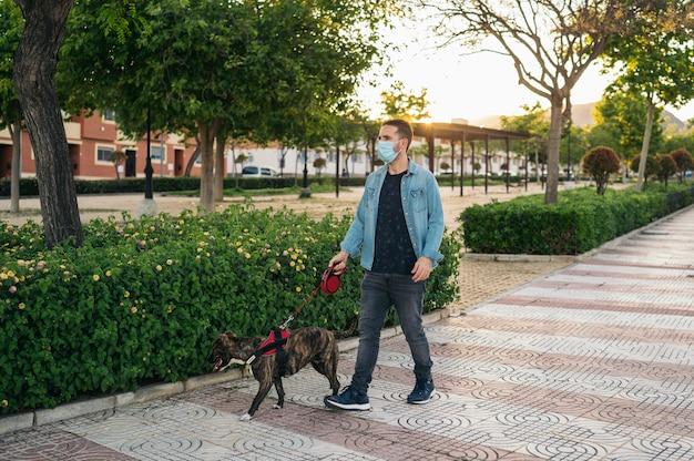 Jovem na máscara médica, passear no parque com seu cachorro