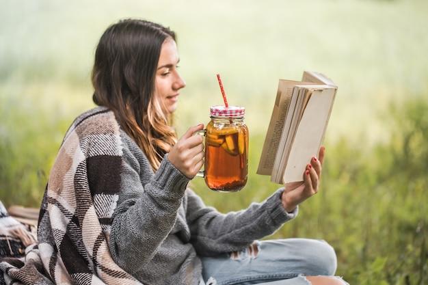 Jovem na natureza com uma bebida na mão lendo um livro
