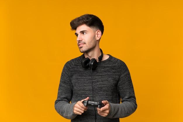 Jovem na parede isolada, jogando videogame