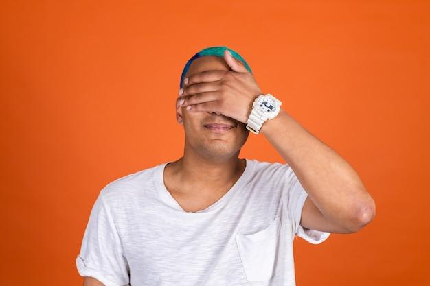 Jovem na parede laranja cobrindo os olhos