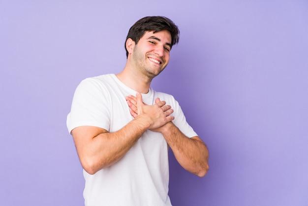 Jovem na parede roxa tem expressão amigável, pressionando a palma da mão no peito