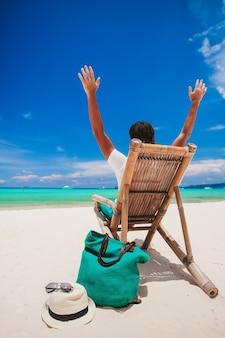 Jovem na praia de areia branca de férias