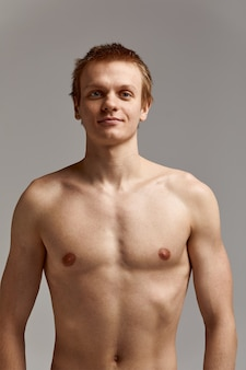 Jovem nadador em excelente forma física, sobre um fundo cinza com espaço de cópia, convite para esportes, banner publicitário.