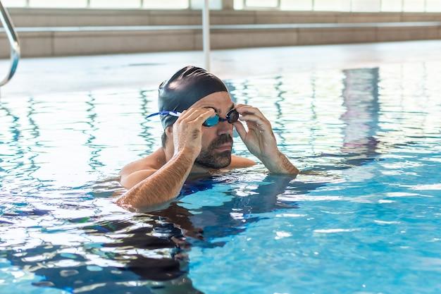 Jovem nadador masculino ajustando seus óculos de proteção para nadar na piscina olímpica