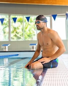 Jovem nadador masculino se preparando para nadar na piscina olímpica