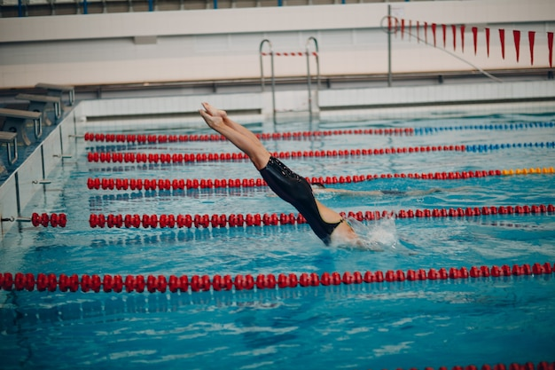 Jovem nadadora pulando na piscina