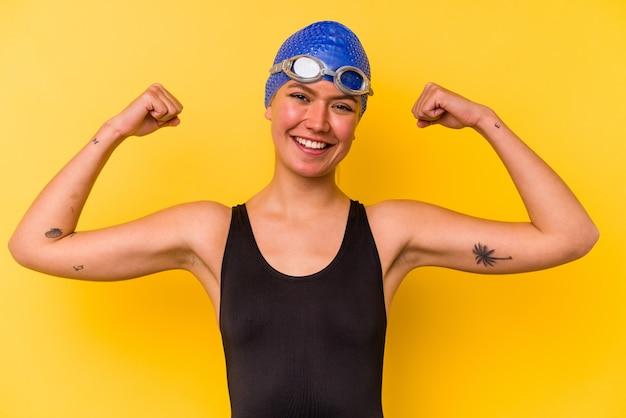 Jovem nadadora venezuelana isolada em fundo amarelo mostrando força gesto com os braços, símbolo do poder feminino