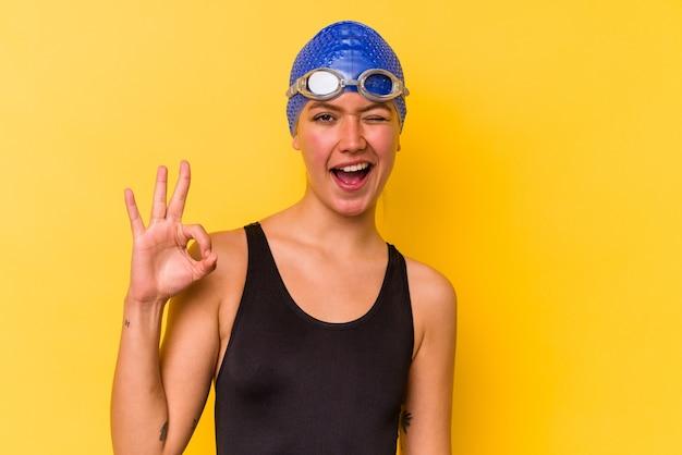 Jovem nadadora venezuelana isolada em uma parede amarela pisca os olhos e faz um gesto de ok com a mão