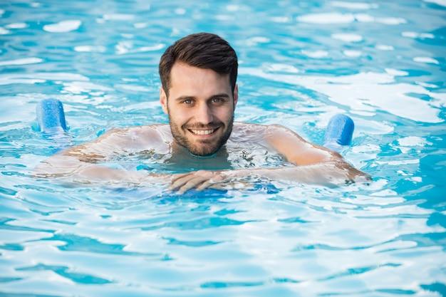 Jovem nadando com tubo inflável na piscina