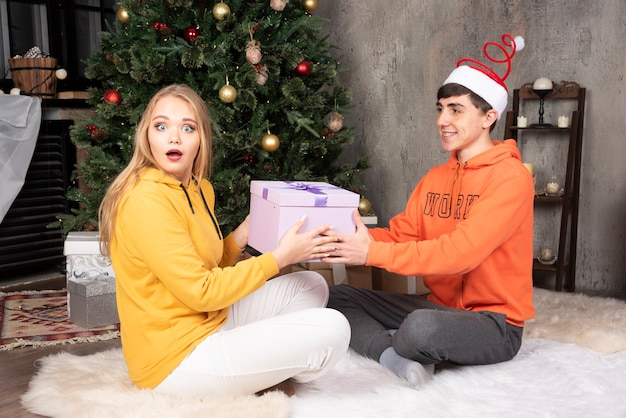 Jovem namorada amorosa presente para o namorado perto da árvore de natal.