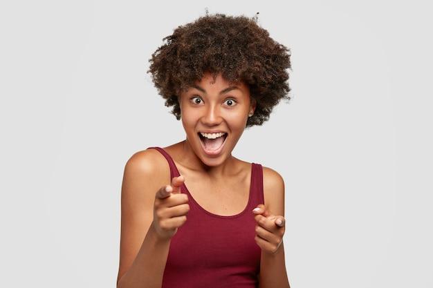 Jovem namorada atraente alegre de pele escura aponta para você, olhando alegre para a câmera
