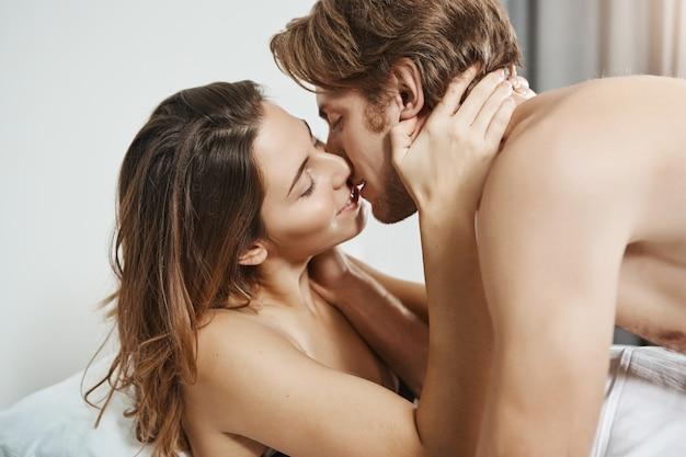 Jovem namorada gostosa beijando cara atraente e segurando as mãos em seu pescoço enquanto estava deitado na cama no meio das preliminares sensuais. casal sexy em relação a ter seu momento no quarto de hotel.