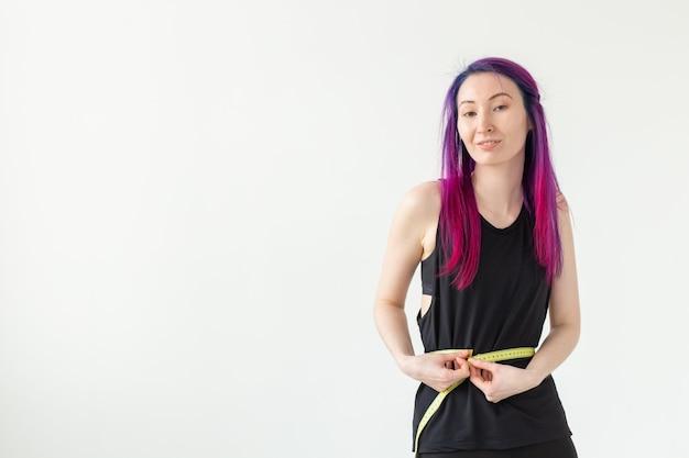 Jovem não identificada hippie com cabelo roxo mede sua cintura com uma fita métrica em um branco