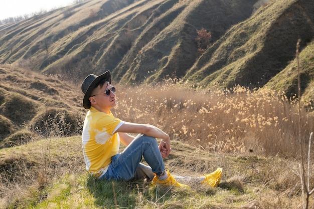 Jovem nas montanhas da primavera ao pôr do sol