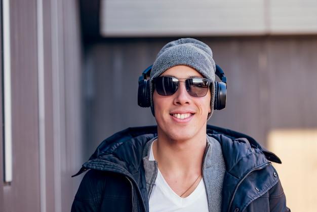 Jovem nas ruas da cidade de inverno com fones de ouvido
