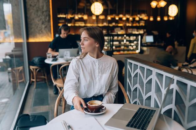 Jovem navegando na internet em um café