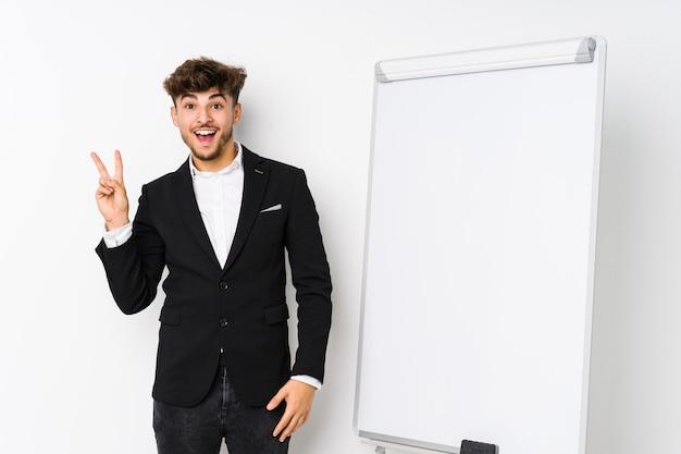 Jovem negócio coaching árabe homem alegre e despreocupado, mostrando um símbolo de paz com os dedos.