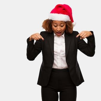 Jovem, negócio, mulher preta, desgastar, um, chirstmas, chapéu santa, apontar baixo