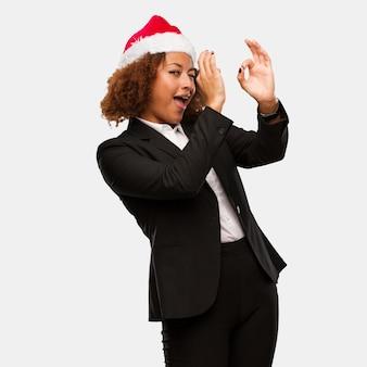 Jovem, negócio, mulher preta, desgastar, um, chirstmas, chapéu santa, fazendo, a, gesto, de, um, spyglass